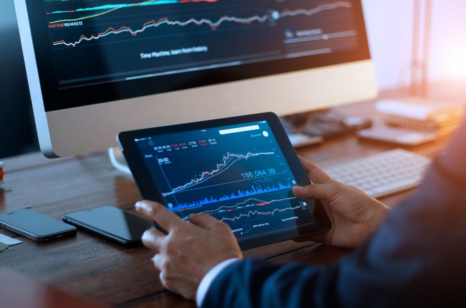 Empresario revisando el mercado de valores en tableta digital y un ordenador de sobremesa con un gráfico de bolsa en pantalla